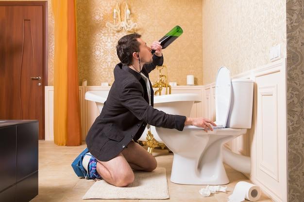 Homme drôle boit de l'alcool assis contre la cuvette des toilettes. intérieur de salle de bain de luxe