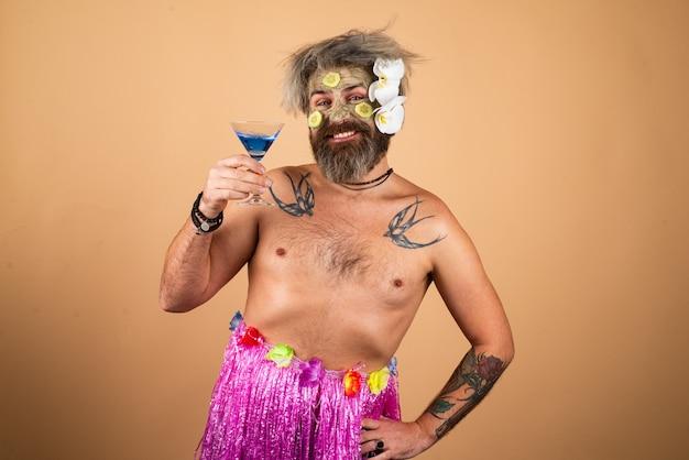 Homme drôle dans le modèle masculin d'hawaï avec masque d'argile et tranches de concombre sur le visage homme ayant une humidité cosmétique...