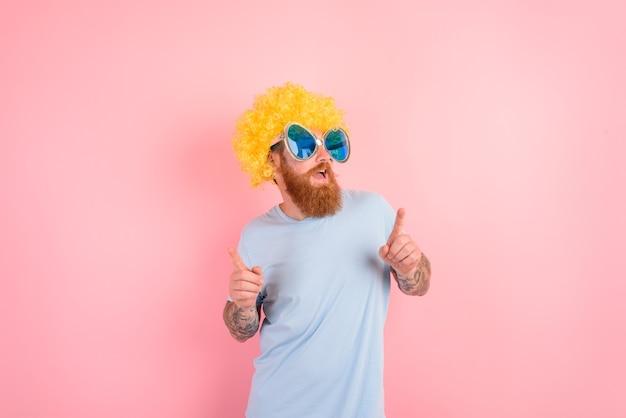 Homme drôle avec des danses de peruke et de lunettes de soleil