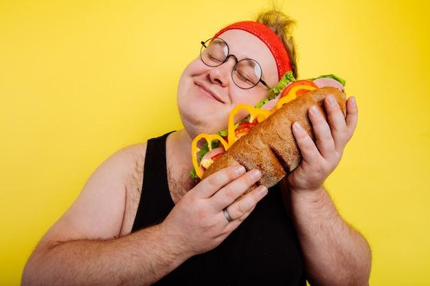 Un homme drôle embrasse un énorme hamburger