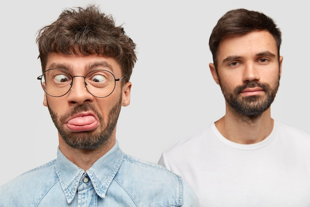 Homme drôle fait la grimace, bête, croise les yeux et montre la langue, son ami barbu se tient dans le mur, a une expression sérieuse