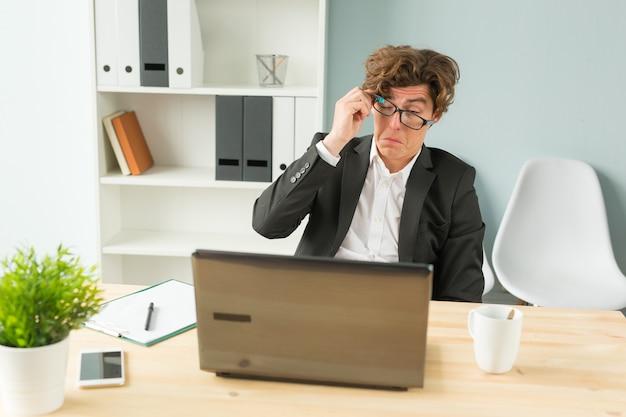 Homme drôle fatigué après avoir travaillé sur ordinateur au bureau