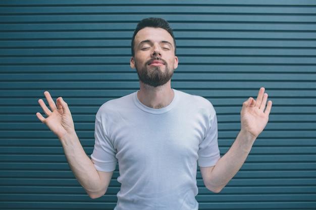 Un homme drôle et insouciant montre ses mains et lève les yeux. il garde les yeux fermés. l'homme médite. isolé sur rayé