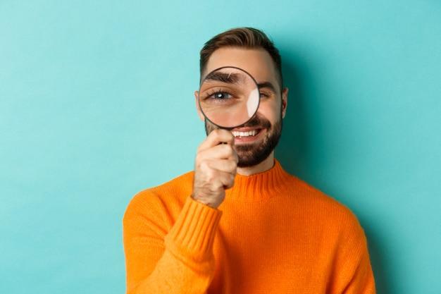 Homme drôle à la loupe, à la recherche ou à l'enquête sur quelque chose, debout en pull orange sur fond turquoise.