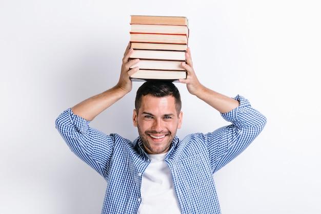 Homme drôle mettant beaucoup de livres à sa tête et regardant joyeusement la caméra. image de l'homme gai isolé sur le mur blanc