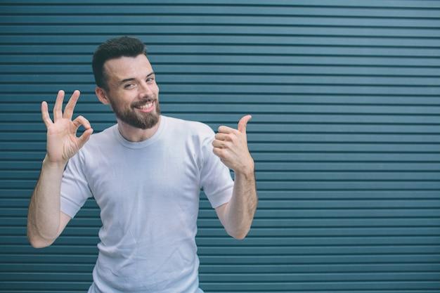 Un homme drôle montre des symboles ok et similaires avec ses mains et ses doigts. homme barbu regarde la caméra et souriant. isolé sur rayé