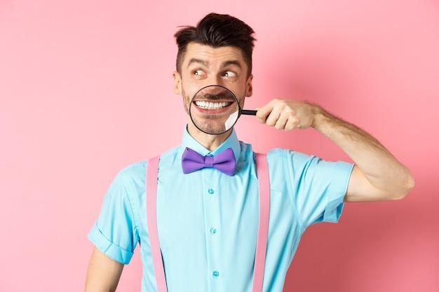 Homme drôle en noeud papillon souriant, montrant les dents avec une loupe et regardant de côté au logo, debout sur le rose.
