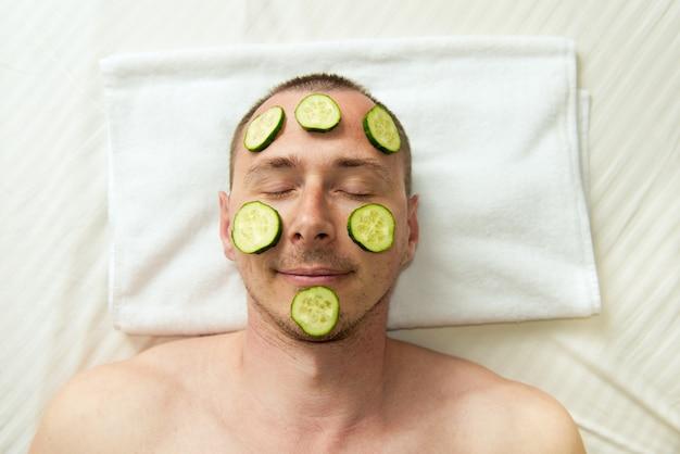Homme drôle recevant un masque facial de concombre procédure cosmétique mans face toilettage lui-même