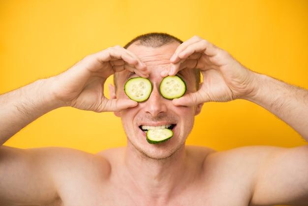 Homme drôle recevant un masque facial de concombre