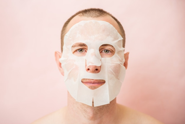 Homme drôle recevant un masque facial nourrissant.