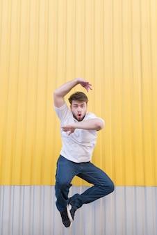 Homme drôle sautant contre le mur jaune