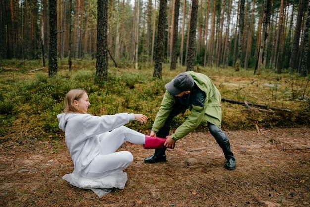 Homme drôle tirant une botte rose de femme drôle dans la forêt