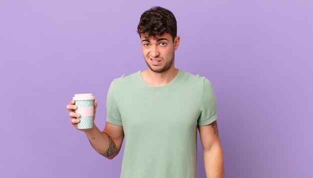 Homme avec du café se sentant perplexe et confus, avec une expression stupide et abasourdie en regardant quelque chose d'inattendu