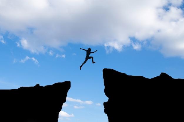 L'homme du courage passe à travers l'écart entre la colline, l'idée de concept d'entreprise
