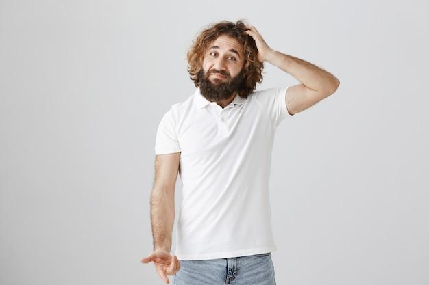 Homme du moyen-orient confus qui hausse les épaules et se gratte la tête indécise