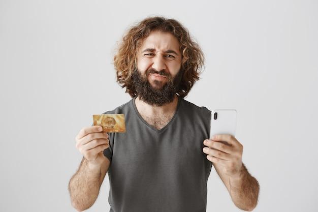 Homme du moyen-orient grimaçant déçu avec carte de crédit et smartphone