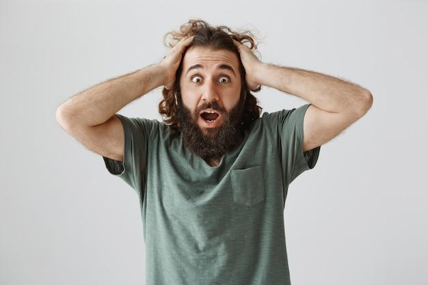 Un homme du moyen-orient haletant choqué à l'air alarmé et inquiet