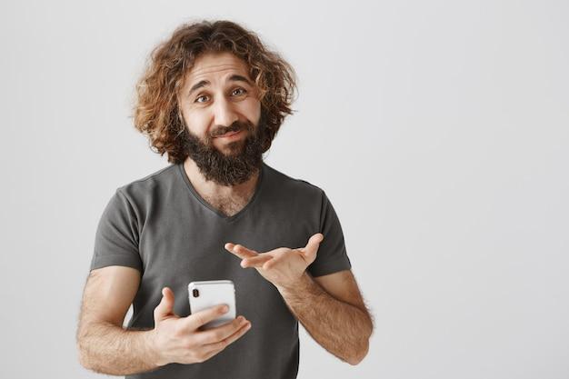 Homme du moyen-orient incertain regardant un téléphone mobile indécis, se sentant hésitant