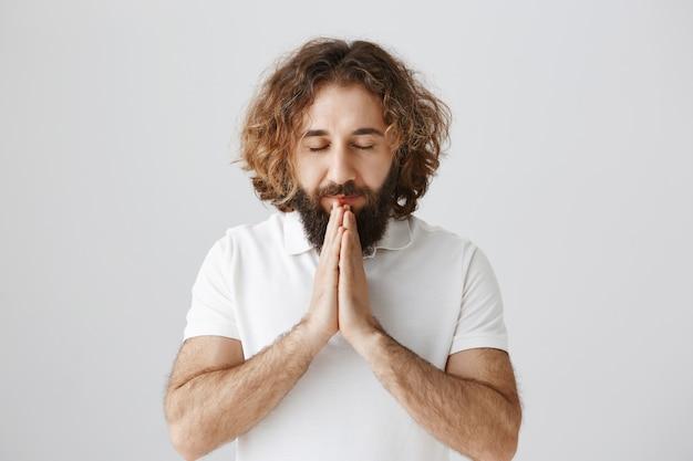 Un homme du moyen-orient plein d'espoir ferme les yeux et prie, se tient la main pour plaider
