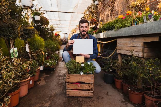 Homme avec du papier près de la boîte avec des fleurs