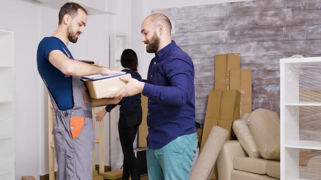 Homme du service de livraison arrivant avec des boîtes et des documents à signer. beau jeune couple emménageant.