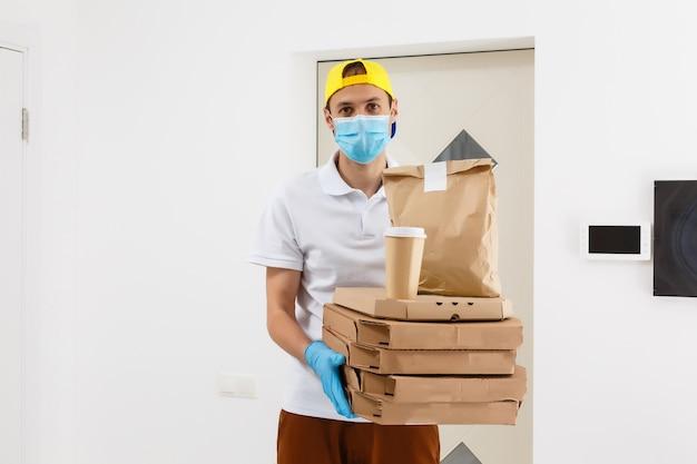 Homme du service de livraison en t-shirt, en masque de protection et gants donnant des commandes de nourriture et tenant des boîtes à pizza sur fond blanc
