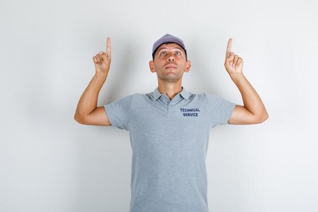 Homme du service technique en t-shirt gris avec capuchon pointant les doigts vers le haut