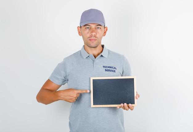 Homme du service technique en t-shirt gris avec casquette tenant tableau noir