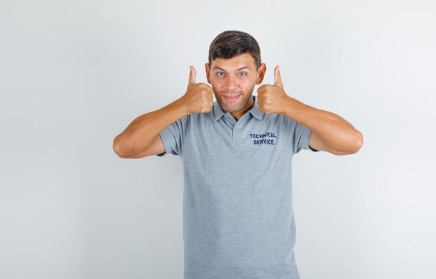 Homme du service technique en t-shirt gris montrant les pouces vers le haut et à la bonne humeur