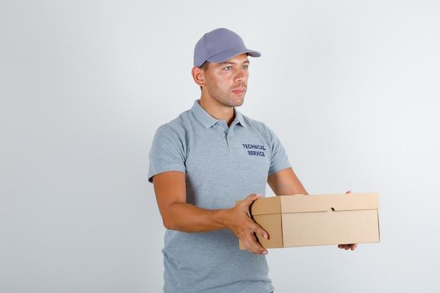 Homme du service technique tenant une boîte en carton en t-shirt gris avec capuchon