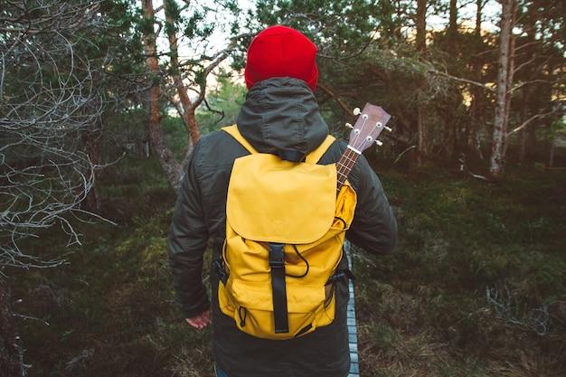 L'homme du voyageur se tient sur un sentier au milieu d'une forêt avec une guitare dans un sac à dos jaune