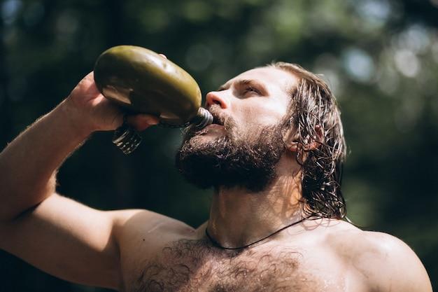 Homme de l'eau potable dans la forêt
