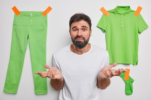 L'homme écarte les paumes se sent douteux hausse les épaules pose sur blanc avec des vêtements verts collés au mur se sent indécis pense incertain