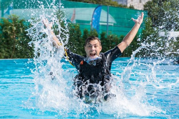 Un homme éclabousse dans la piscine tout en portant une combinaison de plongée