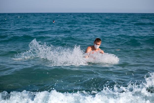 Un homme éclabousse seul en pleine mer portant un masque lors de l'épidémie de grippe covid 19