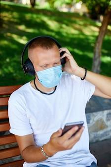 Homme écoutant de la musique avec un casque, à l'aide de smartphone portant un masque de protection du visage en plein air dans le parc