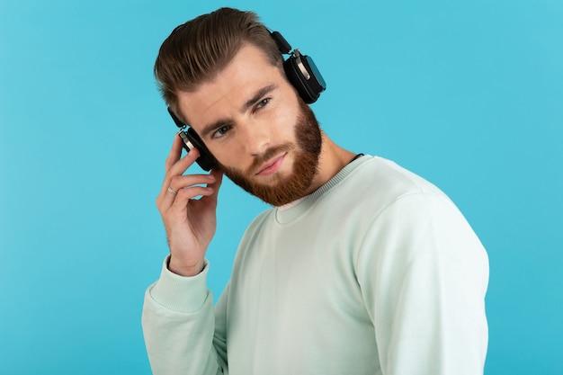 Homme écoutant de la musique sur un casque sans fil isolé sur bleu