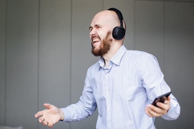 Homme écoutant de la musique sur des écouteurs dans le salon