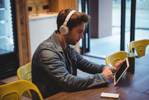 Homme écoutant de la musique avec des écouteurs tout en utilisant une tablette numérique