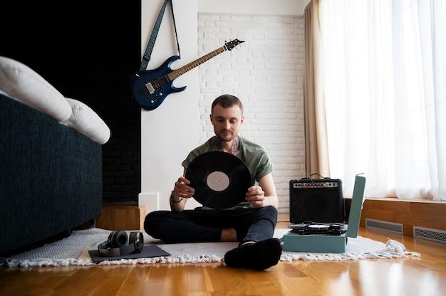 Homme écoutant de la musique à partir d'un disque vinyle