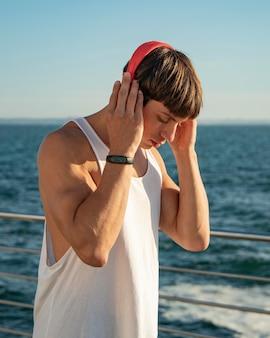 Homme écoutant de la musique à la plage tout en travaillant