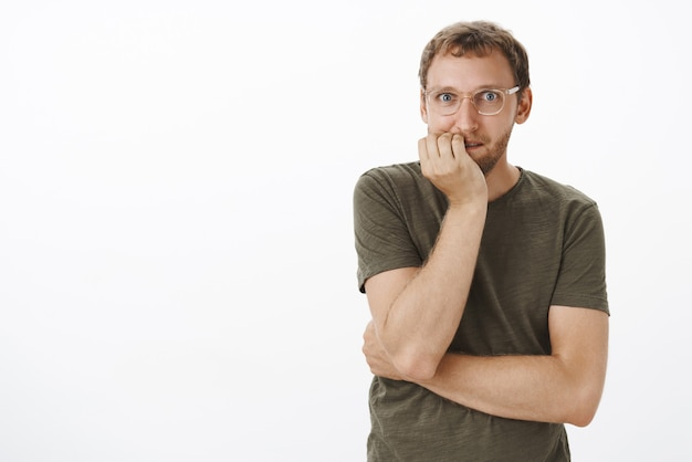 Homme écoutant une rumeur passionnante et intrigante se mordant les ongles de frisson et de stupeur en souriant et en regardant enthousiaste et amusé voulant entendre tous les potins en se tenant debout sur un mur gris