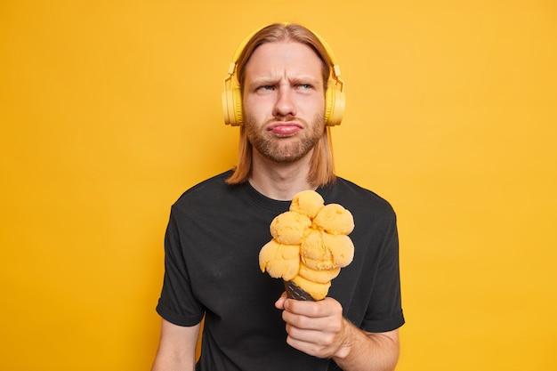 L'homme écoute de la musique via un casque stéréo détient un gros cône de crème glacée appétissante se sent mécontent vêtu d'un t-shirt noir isolé sur jaune