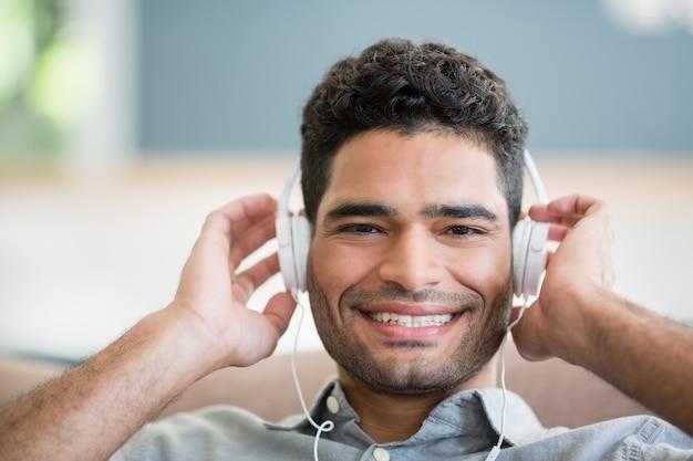 Homme, écouter musique, sur, écouteurs, dans, salle de séjour, chez soi