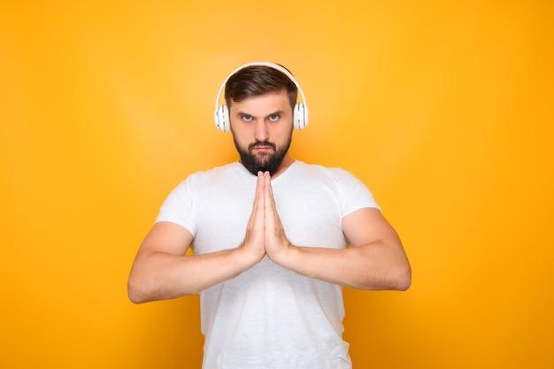 Un homme avec des écouteurs a croisé les mains devant sa poitrine et écoute de la musique.