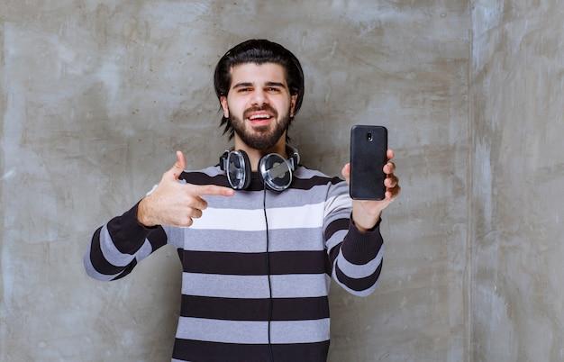 Homme avec des écouteurs démontrant son smartphone noir