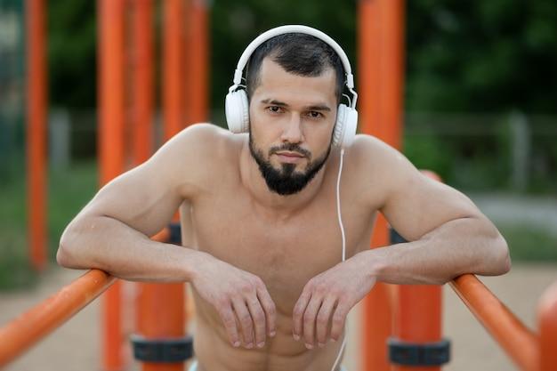 Un homme avec des écouteurs se repose après avoir fait du push ups sur les barres à l'extérieur dans l'après-midi