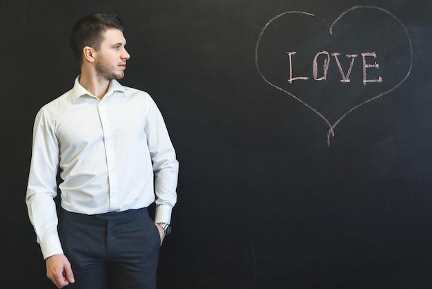 L'homme a écrit l'amour de mot sur le tableau et à la recherche de copyspace