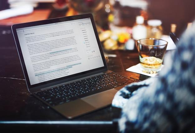 Un homme écrit un article au bar