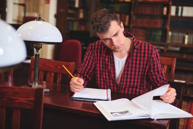 L'homme écrit au bureau dans la bibliothèque